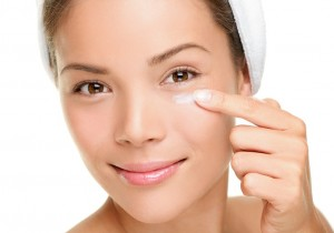 Face cream woman applying skin cream under eyes. Beauty eye contour cream, wrinkle cream or anti-aging skin care cream. Beautiful young mixed race Asian Chinese / Caucasian female beauty model in her 20s isolated on white background.